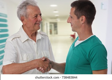 Smiling male doctor giving handshake to senior male patient. Health care concept