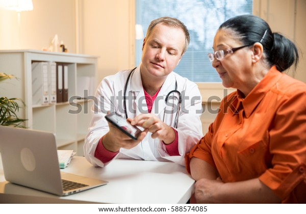 Smiling male doctor holding digital tablet, showing test results to patient in hospital. Sick senior woman having a doctor appointment. Medical consultation.