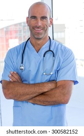 Smiling male doctor looking at camera with arms crossed in medical office