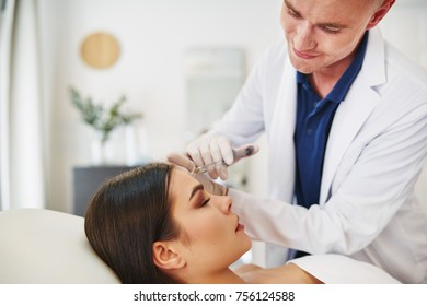 Smiling male doctor performing a injection to the forehead of a woman lying on a table in a beauty clinic
