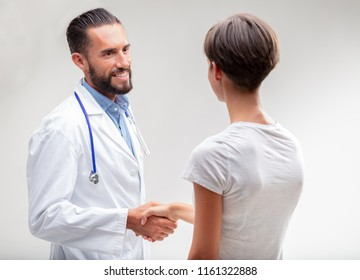 Smiling male doctor shaking hands with a female patient in an over the shoulder view on white