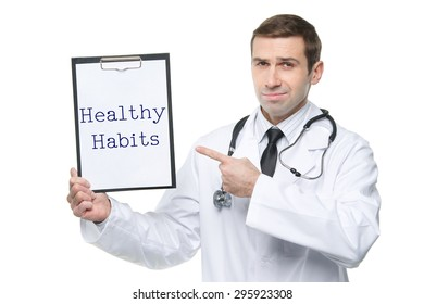 Smiling male doctor with stethoscope pointing forefinger to clipboard with HEALTHY HABITS motivational quote/ Isolated