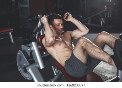 Smiling male is doing efforts with heavy weight in sport center. He is exercising on hack machine for glute relief. Bodybuilder is pushing platform and bending legs