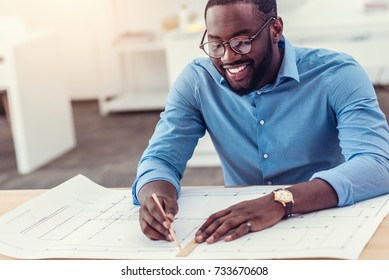 Smiling male engineer working on technical drawing at table