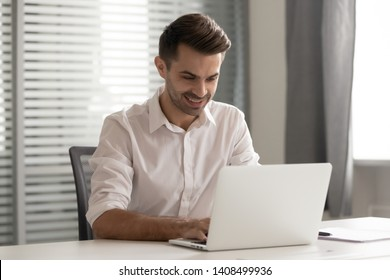 Smiling male entrepreneur working on computer sit at office desk, happy businessman professional typing corporate email using laptop communicating online using software for business at workplace