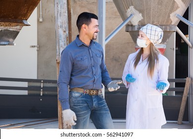 Smiling male farmer and female veterinarian in protective clothing standing in sty