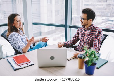 Smiling male and female colleagues joking during communication in office planning strategy for cooperation,prosperous employees making creative decisions for common startup sitting at desktop