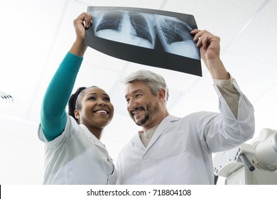 Smiling Male And Female Doctors Examining Chest X-ray In Hospita