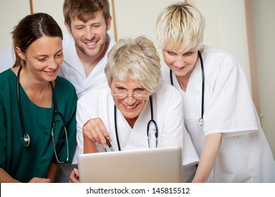 Smiling male and female doctors looking at laptop in hospital