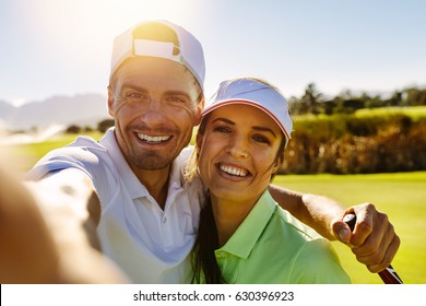 Smiling male and female golfers taking selfie at field on sunny day. Happy young couple taking self portrait at golf course.