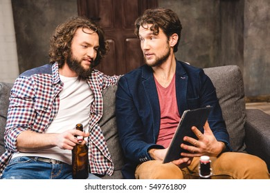 Smiling male friends sitting on sofa and using digital tablet