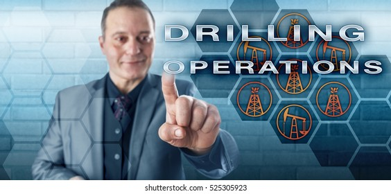 Smiling male industrial manager pressing DRILLING OPERATIONS on a virtual control screen. Petroleum industry concept and fossil fuel metaphor for drilling technology, derrick, pumpjack and oil wells.
