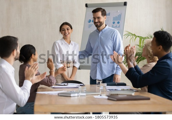 Smiling male leader praising happy millennial arab colleague at group meeting. Smiling diverse coworkers applauding, supporting new worker or congratulating with personal professional achievement.