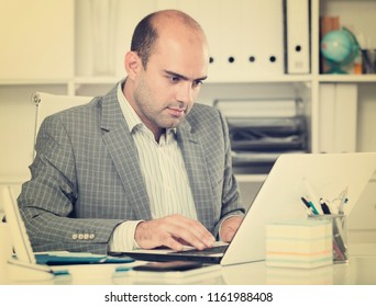 Smiling male office worker drinking water and working at the laptop