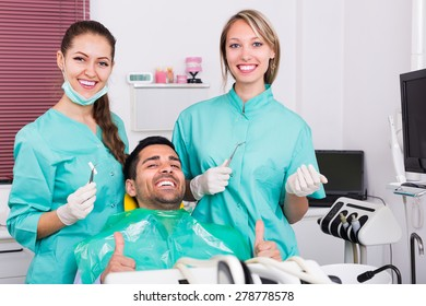 Smiling male patient and dentist with assistant during check up at dental clinic