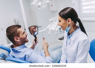 smiling male patient looking in the mirror cheking teeth after dental procedure in clinic