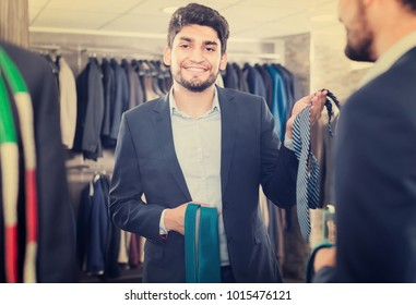 Smiling male is picking up tie for jacket in front of the mirror in men's shop.