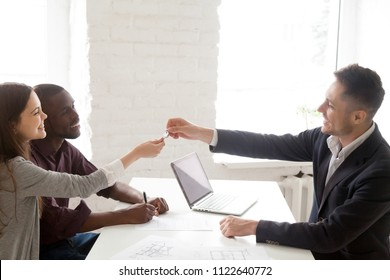 Smiling male real estate agent giving keys to millennial multiethnic couple buying first home together, clients becoming owners of shared apartment, excited spouses purchasing property from realtor