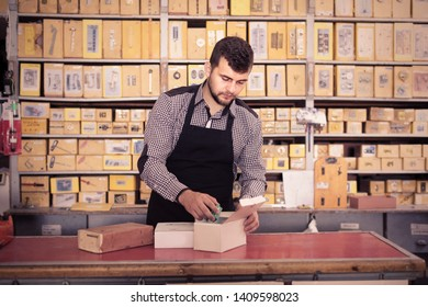 Smiling male seller sorting boxes with door details in houseware shop