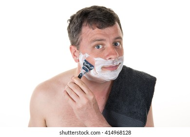 Smiling male shaving with a razor looking at you
