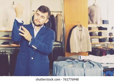 Smiling male shopper choosing fashion jacket in men store