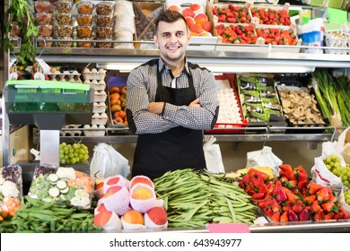 smiling male shopping assistant demonstrating assortment of grocery shop