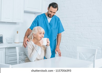 smiling male social worker looking at senior woman drinking tea in kitchen