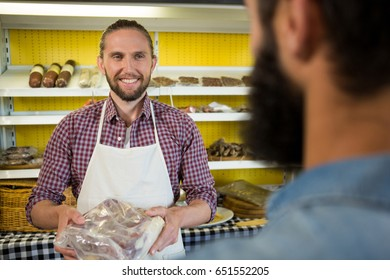 Smiling male staff holding a meat packet at counter in market
