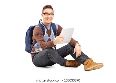 Smiling male student with backpack seated on a floor holding a tablet isolated against white background