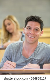Smiling male student during class at the lecture hall