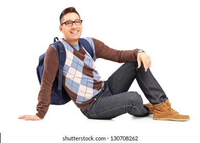 Smiling male student sitting on the floor, isolated on white background