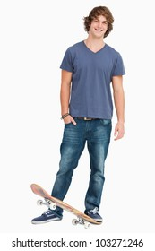 Smiling male student with a skateboard against white background