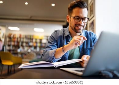 Étudiant souriant travaillant et étudiant dans une bibliothèque