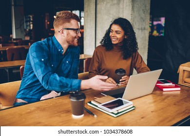 Smiling male teacher with red hair explaining new topic for study to cheerful african american student sitting at laptop computer in coworking.Two hipsters discussing new project during collaboration