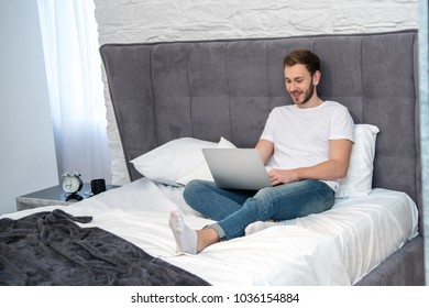Smiling male using laptop in bedroom with modern interior