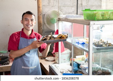 smiling male waiters carrying trays of side dishes near the display windows in food stalls