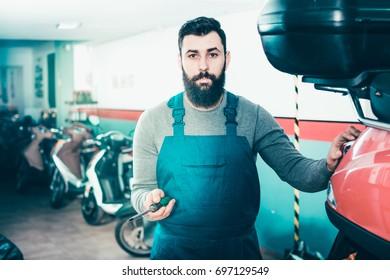 Smiling male worker repairing scooters in motorcycle garage