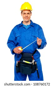 Smiling male worker wearing yellow safety hat holding measuring tape