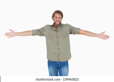 Smiling man with arms open wide on white background