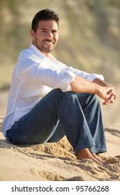 smiling man at the beach seated on the sand