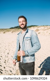 Smiling man with a beer on the beach in a sunny day