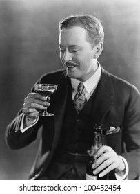 Smiling man with beverage and bottle