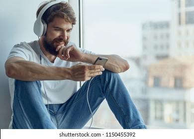 smiling man in big headphones looking into the phone