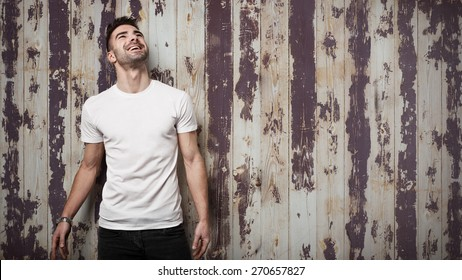 Smiling man in blank t-shirt, grunge wooden wall background