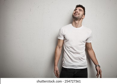 Smiling man in blank t-shirt, white grunge wall background