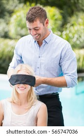 Smiling man blindfolding woman at poolside