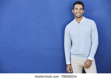 Smiling man in blue sweater against blue wall, portrait