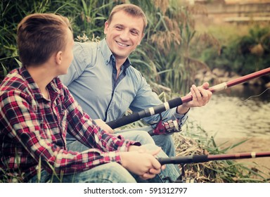 Smiling man and boy fishing together on freshwater river from shore