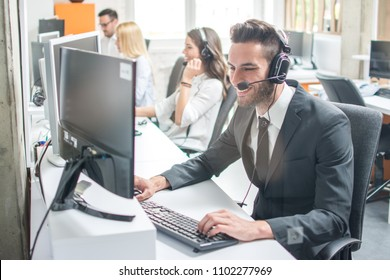 Smiling man in business wear with headset working on desktop computer in customer service call support helpline business center