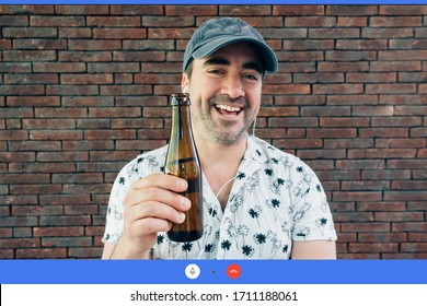 smiling man chatting in a video call using earphones. Happy and cool person drinking a beer with friends using technology during lockdown isolation
